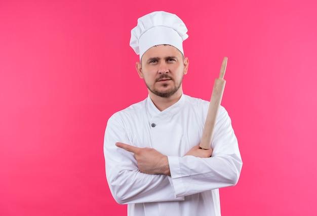 Уверенный молодой красивый повар в униформе шеф-повара держит скалку, указывая на сторону, изолированную на розовой стене