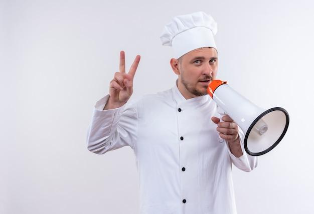 シェフの制服を着た自信のある若いハンサムな料理人がスピーカーを持ち、白い壁にピースサインをしている