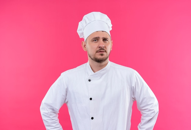 Уверенный молодой красивый повар в униформе шеф-повара изолирован на розовой стене