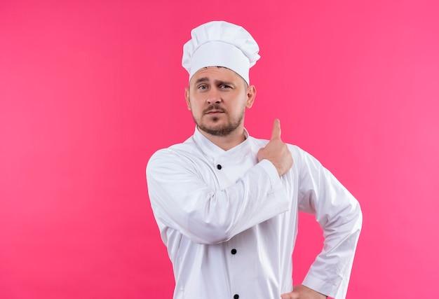 Уверенный молодой красивый повар в униформе шеф-повара, указывая позади изолированной на розовой стене