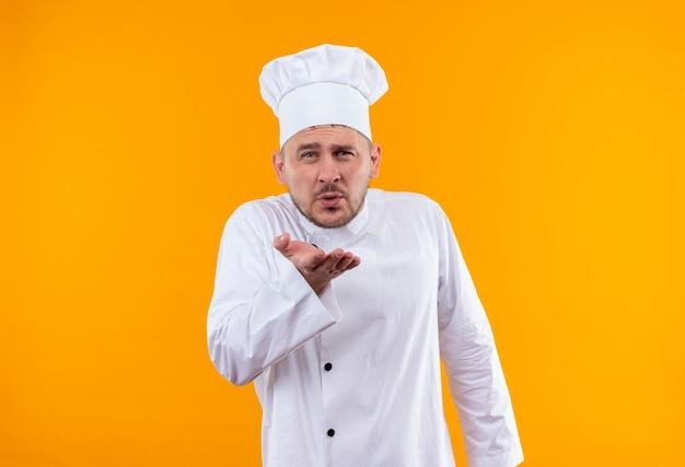 オレンジ色の壁に孤立した打撃のキスを送るシェフの制服を着た自信のある若いハンサムな料理人