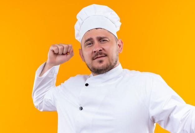 オレンジ色の壁に上げられた握りこぶしでシェフの制服を着た自信のある若いハンサムな料理人