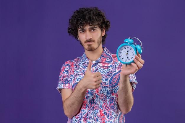 コピースペースと孤立した紫色のスペースに親指を示す目覚まし時計を保持している自信を持って若いハンサムな巻き毛の旅行者の男