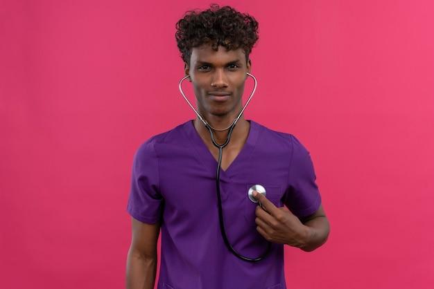 Un giovane medico dalla carnagione scura bello fiducioso con capelli ricci che indossa l'uniforme viola usando lo stetoscopio per controllare il battito cardiaco