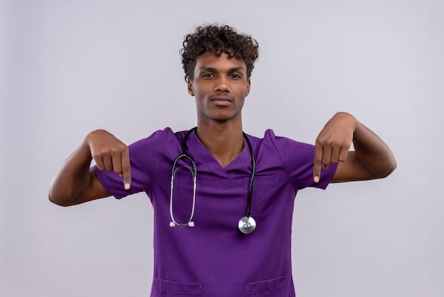 Un fiducioso giovane medico dalla carnagione scura bello con capelli ricci che indossa l'uniforme viola con lo stetoscopio rivolto verso l'alto con le dita indice