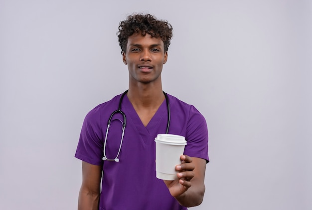 Un giovane medico dalla carnagione scura bello fiducioso con capelli ricci che indossa l'uniforme viola con lo stetoscopio che mostra la tazza di caffè di carta