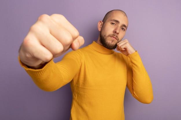 보라색에 고립 된 카메라에 주먹을 들고 싸우는 포즈 서 자신감 젊은 잘 생긴 남자