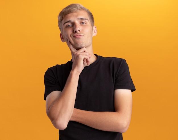 Fiducioso giovane bel ragazzo che indossa la camicia nera che mette il dito sulla guancia isolata sulla parete gialla