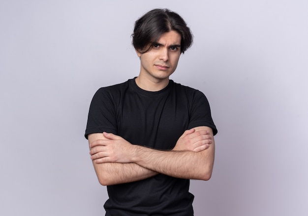 Уверенный молодой красивый парень в черной футболке, скрестив руки, изолированные на белой стене