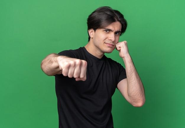 녹색 벽에 고립 된 포즈 싸움에 검은 티셔츠 서 입고 자신감 젊은 잘 생긴 남자