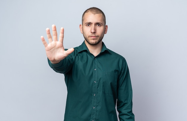 Confident young handsome guy wearing green shirt showing five