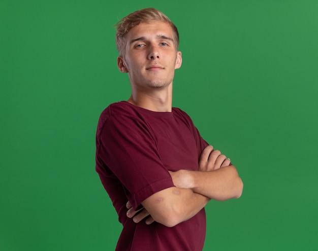 녹색 벽에 고립 된 손을 건너 빨간 셔츠를 입고 자신감 젊은 잘 생긴 남자