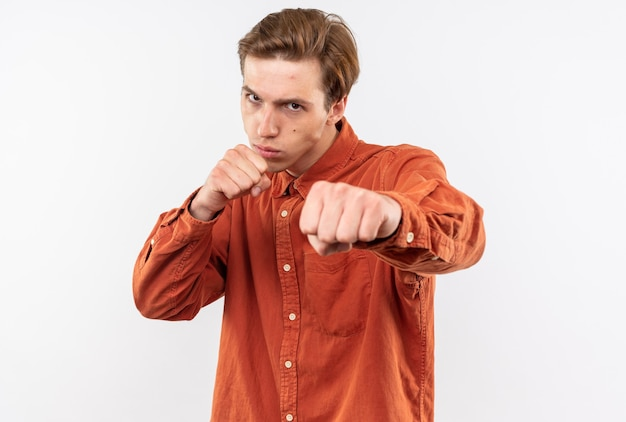 Confident young handsome guy wearing red shirt standing in fighting pose isolated on white wall