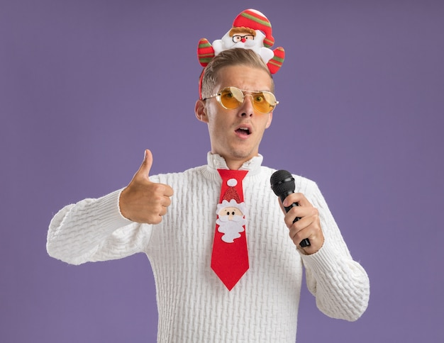 Confident young handsome guy wearing santa claus headband and tie with glasses holding microphone looking at camera showing thumb up isolated on purple background