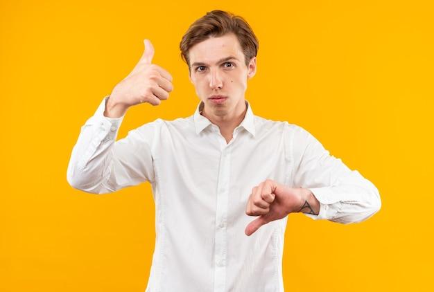 Fiducioso giovane bel ragazzo che indossa una camicia bianca che mostra i pollici su e giù