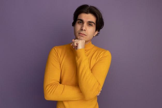 Fiducioso giovane bel ragazzo che indossa un maglione dolcevita giallo mettendo la mano sotto il mento isolato sulla parete viola