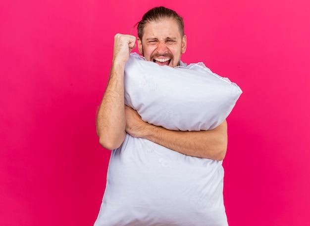 Fiducioso giovane uomo malato bello abbracciando cuscino guardando davanti mantenendo il pugno in aria urlando isolato sulla parete rosa