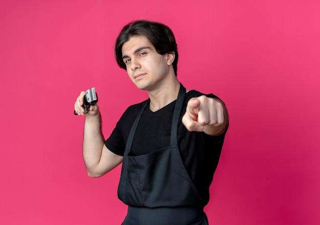 머리 가위를 잡고 분홍색 벽에 고립 된 제스처를 보여주는 제복을 입은 자신감이 젊은 잘 생긴 남성 이발사