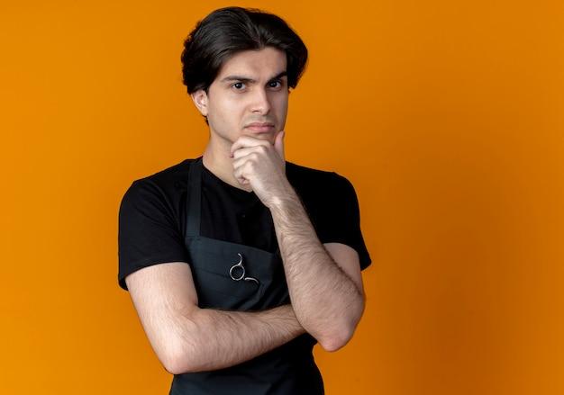 오렌지 벽에 고립 된 턱에 손을 넣어 제복을 입은 자신감이 젊은 잘 생긴 남성 이발사