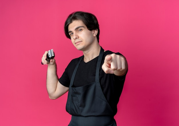 Confident young handsome male barber in uniform holding hair clippers and showing you gesture isolated on pink wall