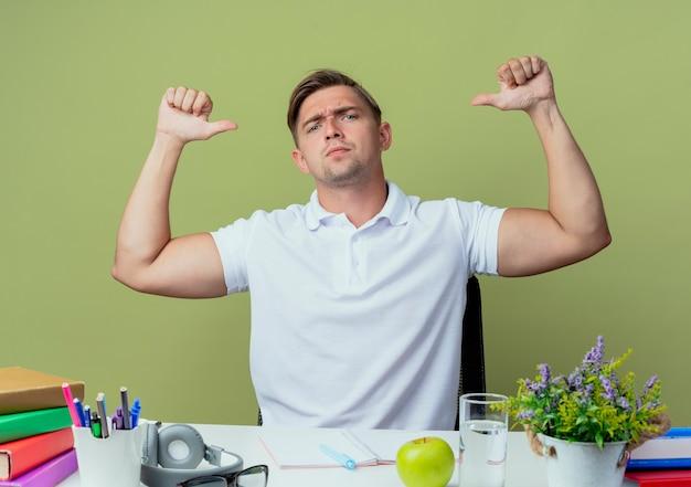 올리브 그린에 고립 된 자신의 학교 도구 포인트와 책상에 앉아 확신 젊은 잘 생긴 남자 학생