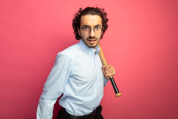 Confident young handsome man wearing glasses holding baseball bat looking at front isolated on pink wall