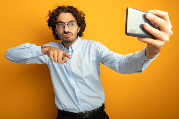 Fiducioso giovane uomo bello con gli occhiali prendendo selfie che punta al telefono isolato sulla parete arancione