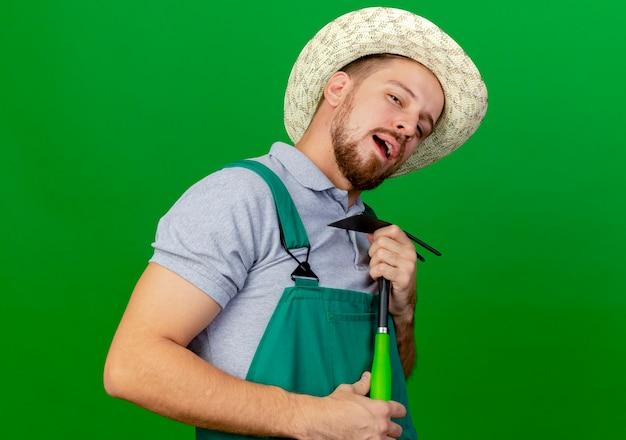 Уверенный молодой красивый славянский садовник в униформе и шляпе, держащий грабли, притворяется, что поет, используя грабли в качестве микрофона