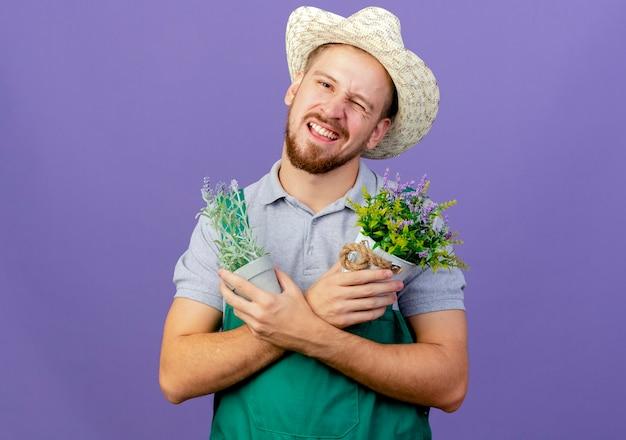 自信を持って若いハンサムなスラブの庭師の制服と帽子を握って手を交差させて植木鉢を持って紫色の壁に隔離されたコピースペース