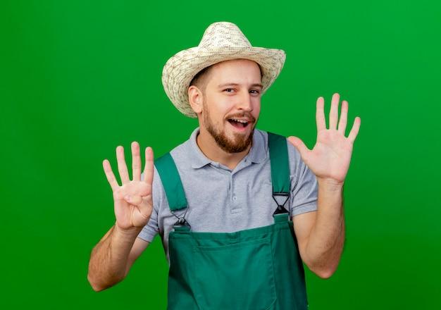 Уверенный молодой красивый славянский садовник в униформе и шляпе смотрит с пустыми руками