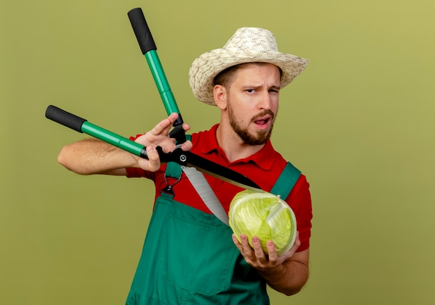 Confident young handsome slavic gardener in uniform and hat holding cabbage and trying to cut it with pruners  isolated on olive green wall with copy space