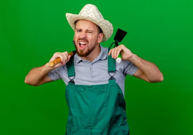 Fiducioso giovane giardiniere slavo bello in uniforme e cappello che tiene zappa-rastrello e rastrello sulle spalle alla ricerca
