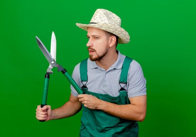 Confident young handsome slavic gardener in uniform and hat looking holding pruners