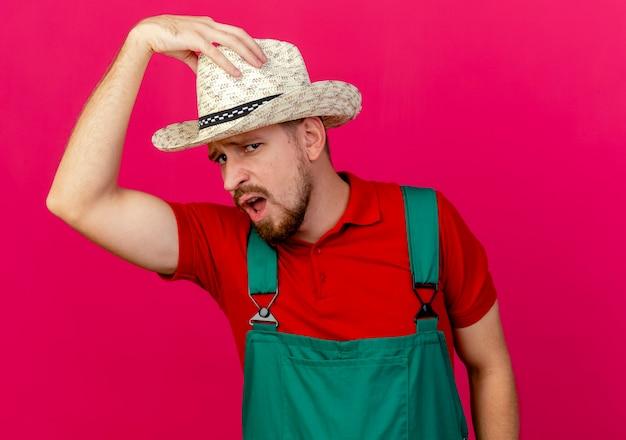 Fiducioso giovane giardiniere slavo bello in uniforme e cappello guardando toccando il suo cappello