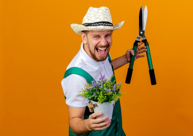 Confident young handsome slavic gardener in uniform and hat standing in profile view holding flower plant and pruners looking screaming isolated