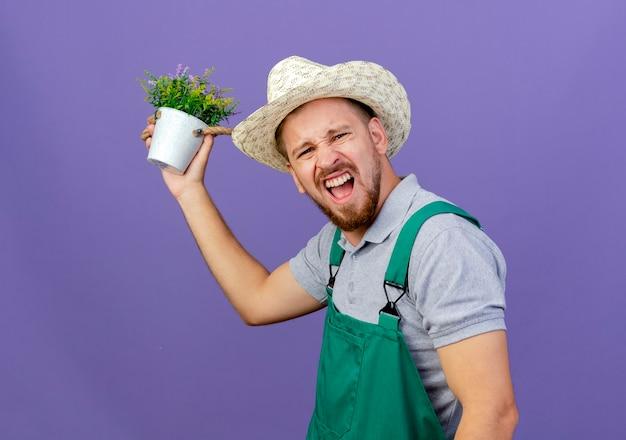 Fiducioso giovane giardiniere slavo bello in uniforme e cappello in piedi in vista di profilo che tiene il vaso di fiori che sembra isolato sulla parete viola con lo spazio della copia
