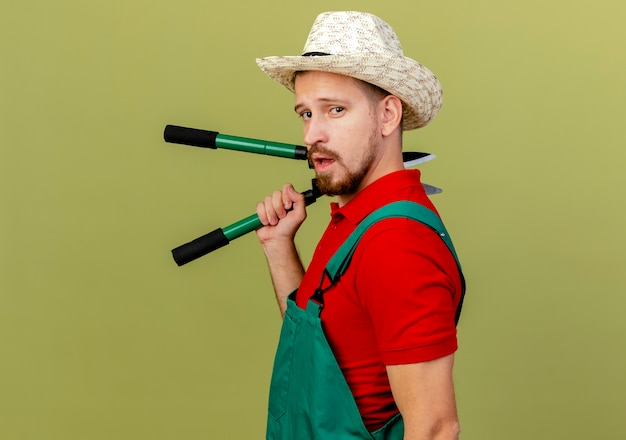 Confident young handsome slavic gardener in uniform and hat standing in profile view holding pruners looking isolated