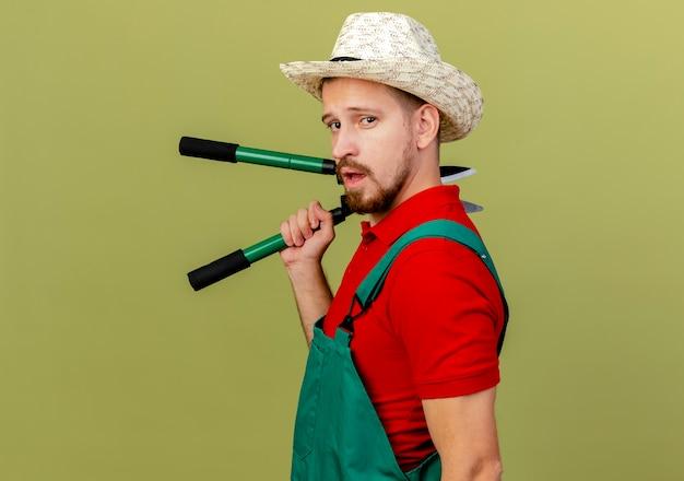 Fiducioso giovane giardiniere slavo bello in uniforme e cappello in piedi in vista di profilo tenendo i potatori che sembrano isolati