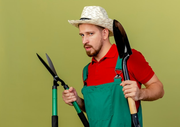 Confident young handsome slavic gardener in uniform and hat standing in profile view holding pruners and spade  isolated on olive green wall