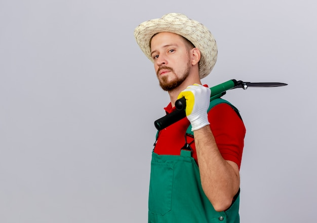 Confident young handsome slavic gardener in uniform and hat standing in profile view looking holding pruners on shoulder isolated