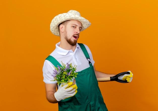 Giovane giardiniere slavo bello sicuro in cappello da portare uniforme e guanti da giardinaggio che tengono vanga e vaso da fiori che sembrano isolati
