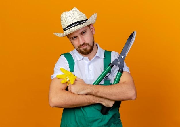 Fiducioso giovane bello giardiniere slavo in uniforme che indossa il cappello in piedi con la postura chiusa tenendo i guanti da giardinaggio e potatori cercando isolato
