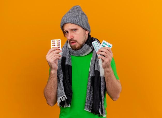 コピースペースとオレンジ色の壁に分離されたカプセルのパックを保持している冬の帽子とスカーフを身に着けている自信を持って若いハンサムなスラブの病気の男