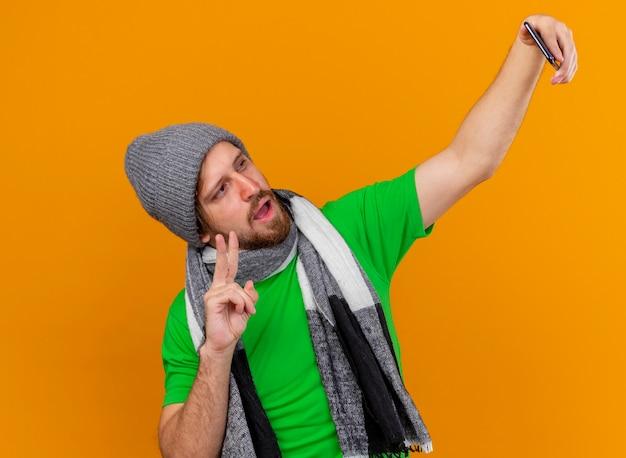 冬の帽子とスカーフを身に着けている自信を持って若いハンサムなスラブの病気の男は、オレンジ色の壁に分離されたピースサインをやって自分撮りをしています
