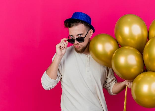 パーティーハットとサングラスを身に着けている自信を持って若いハンサムなスラブ党の男は、コピースペースでピンクの壁に分離された正面を見て風船をつかんでメガネをつかむ