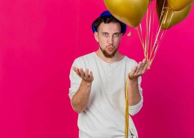 Fiducioso giovane ragazzo slavo bello del partito che indossa il cappello del partito che tiene i palloncini guardando davanti mostrando la mano vuota facendo gesto di bacio isolato sulla parete rosa con lo spazio della copia