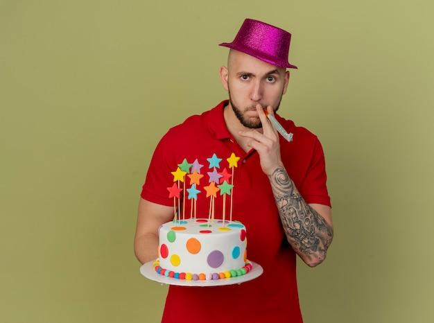 복사 공간 올리브 녹색 배경에 고립 입에 파티 송풍기를 들고 카메라를보고 생일 케이크를 들고 파티 모자를 쓰고 자신감 젊은 잘 생긴 슬라브 파티 남자