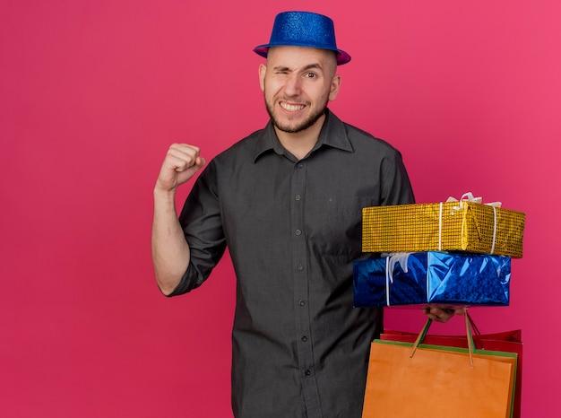Уверенный молодой красивый славянский тусовщик в шляпе, держащий подарочные пакеты и бумажные пакеты