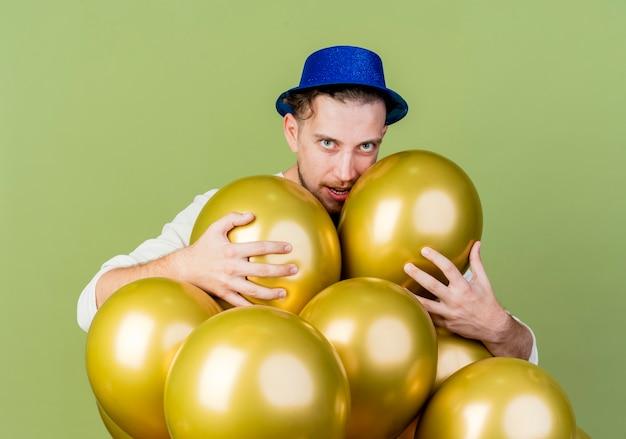 站立在劫掠他们的气球后的自信的党帽子佩带的党帽子劫掠他们看照相机隔绝在橄榄色的绿色背景