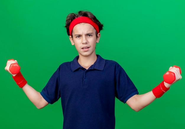녹색 벽에 고립 된 전면을보고 아령을 들고 치과 교정기와 머리띠와 팔찌를 입고 자신감 젊은 잘 생긴 스포티 한 소년